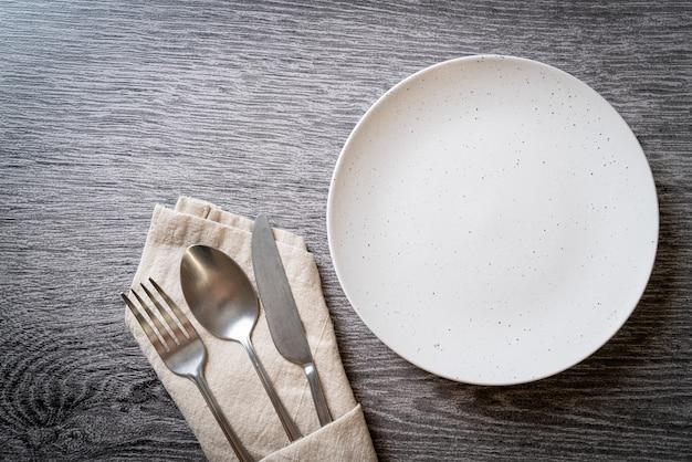 Prato vazio ou prato com faca, garfo e colher no fundo de ladrilhos de madeira