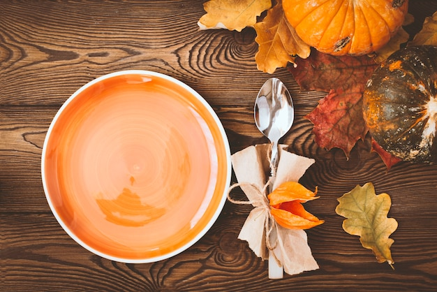Prato vazio pronto para colocação de alimentos, talheres, folhas coloridas em uma mesa de madeira e abóbora. mesa de outono.