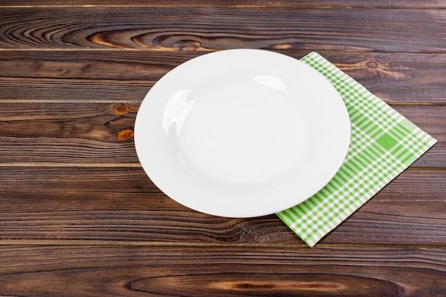 Prato vazio sobre a superfície da mesa de madeira. ver os de cima com espaço para texto