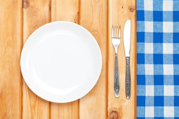 Prato vazio, talheres e toalha sobre o fundo da mesa de madeira. vista de cima com espaço de cópia