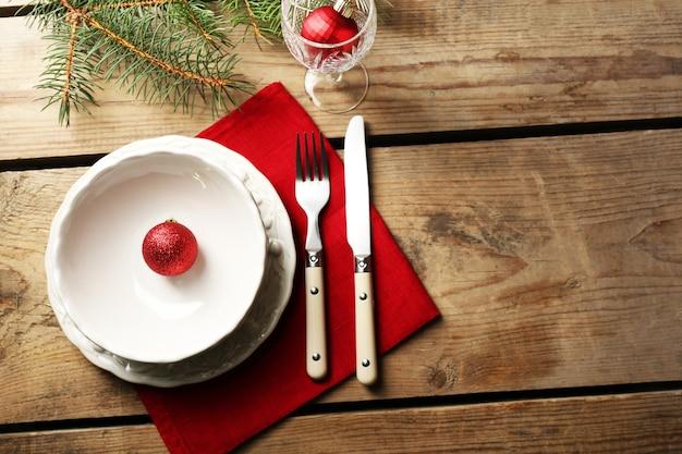 Prato vazio, talheres, guardanapo e copo em fundo de madeira rústico. conceito de configuração de mesa de natal