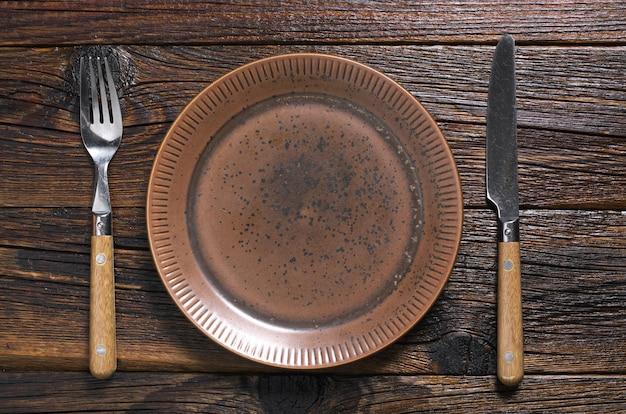 Prato vazio velho com talheres na mesa de madeira escura. vista do topo