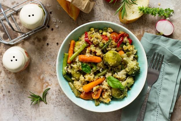 Prato vegano com dieta saudável, cuscuz e vegetais em um fundo de pedra ou ardósia. vista superior
