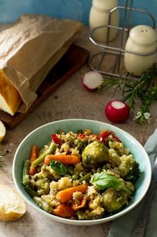 Prato vegano com dieta saudável, cuscuz e vegetais em um fundo de pedra