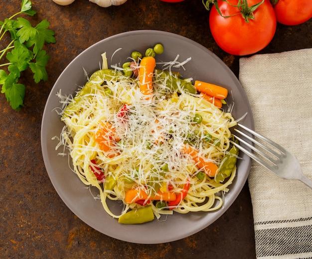 Prato vegetariano, de, macarronada, com, legumes, ervilhas, cenouras, pimenta, e, queijo ralado, topo, vie