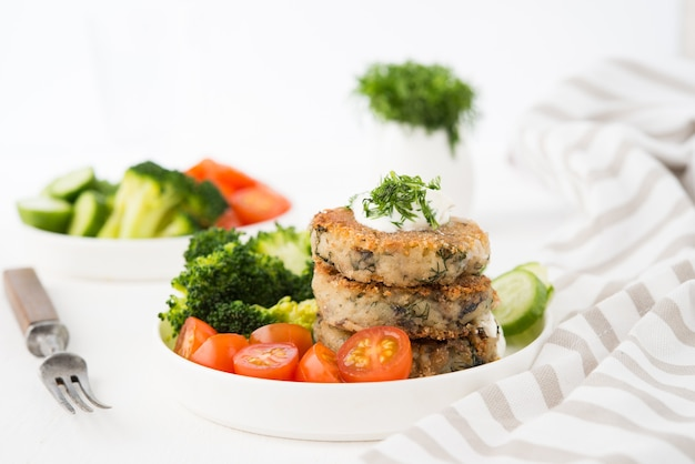 Prato vegetariano de rissóis de batata com ervas e vegetais em um prato