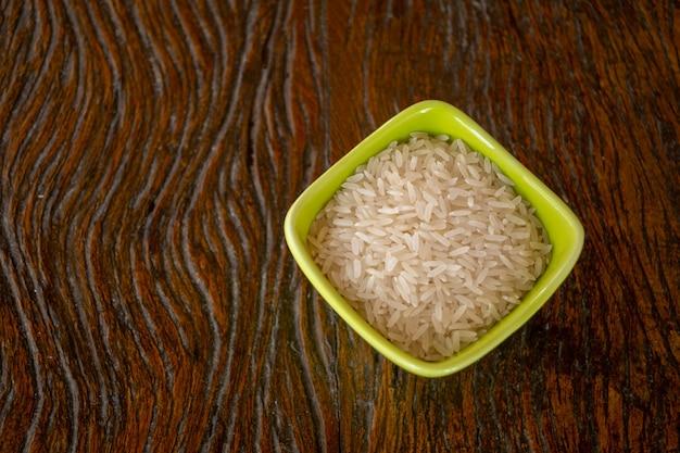 Prato verde com grãos de arroz branco na mesa de madeira