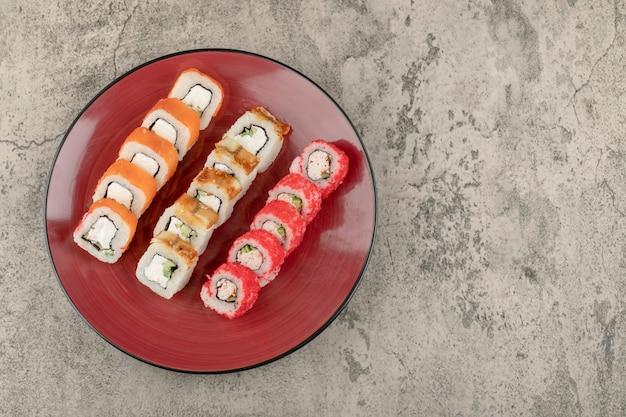 Prato vermelho com vários deliciosos rolos de sushi no fundo de mármore