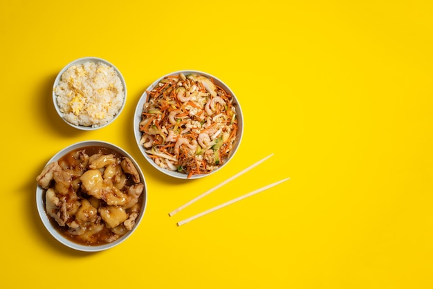 Prato vibrante de salada de camarão, frango crocante, tigela de arroz com ovo e pauzinhos no fundo amarelo. leve comida embora.