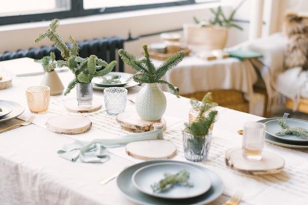 Pratos azuis, talheres de ouro, um galho de abeto em um prato, galhos de pinheiro em vasos.