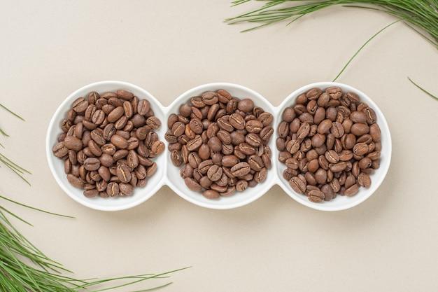 Pratos brancos cheios de grãos de café frescos em uma superfície bege