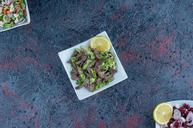 Pratos brancos de saladas de carne e vegetais.