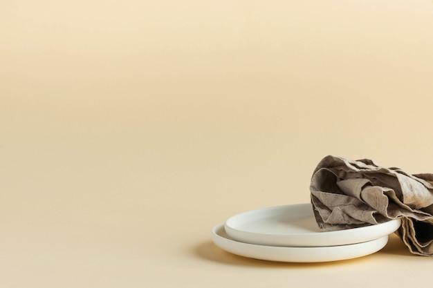 Pratos brancos vazios com um guardanapo de linho em um espaço de cópia minimalista de fundo bege