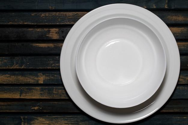 Pratos brancos vazios em uma mesa de madeira