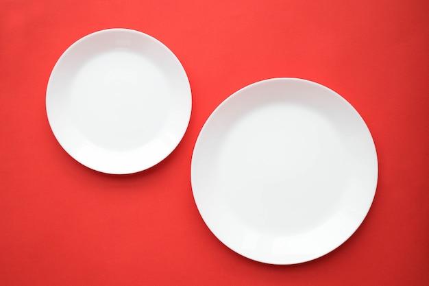 Pratos brancos vazios em uma mesa vermelha, vista superior