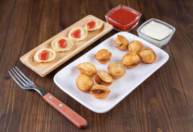 Pratos com bolinhos de carne cozidos e fritos na superfície de madeira com ketchup.