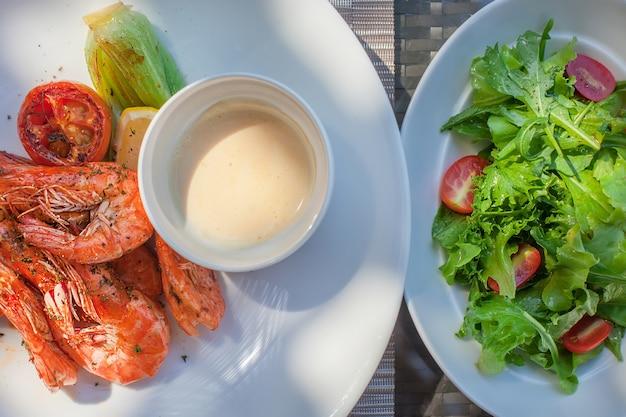Pratos com camarão grelhado e salada com tomate