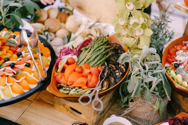Pratos com caprese e legumes cozidos na mesa com pãezinhos e flores em potes