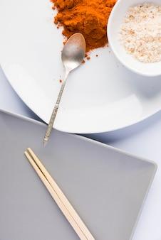 Pratos com especiarias e placa com pauzinhos