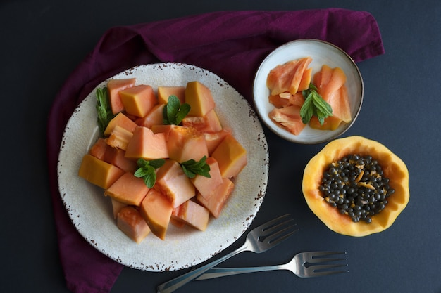 Pratos com frutas mamão fatiado no prato frutas tropicais vista superior