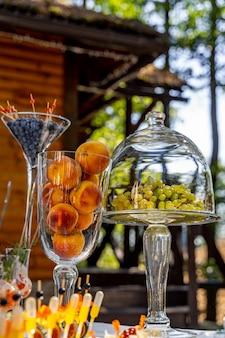 Pratos com mirtilos e pêssegos. frutas na mesa da festa. uvas sob cobertura de cúpula de vidro transparente. sobremesa na mesa festiva.