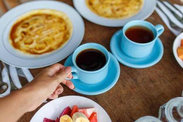 Pratos com panquecas de banana, frutas tropicais e duas xícaras de café na mesa de madeira.