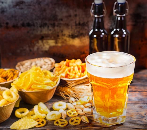 Pratos com petiscos perto de duas garrafas e um copo de cerveja, trigo, nozes e pretzels espalhados na mesa de madeira escura. conceito de alimentos e bebidas