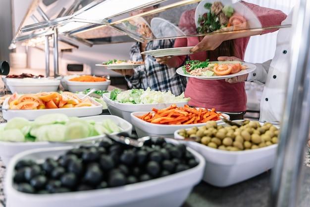 Pratos com pimenta picada, tomate, azeitona e salada em um balcão de restaurante self-service