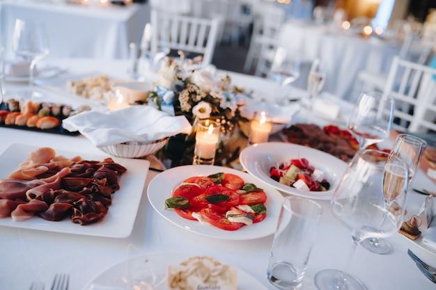 Pratos com salada de legumes, tomate fatiado, presunto e sushi em mesa festiva