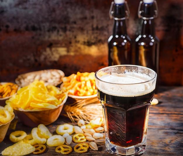 Pratos com salgadinhos perto de duas garrafas e um copo de cerveja escura recém-derramada, trigo, nozes e pretzels espalhados na mesa de madeira escura. conceito de alimentos e bebidas