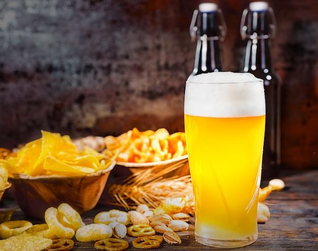 Pratos com salgadinhos perto de duas garrafas e um copo de cerveja light não filtrada, trigo, nozes espalhadas e pretzels na mesa de madeira escura. conceito de alimentos e bebidas
