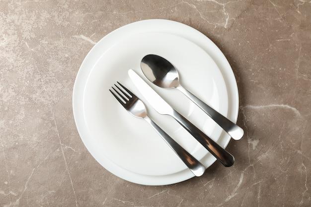 Pratos com talheres na cor cinza, vista superior