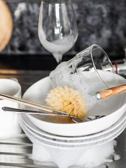 Pratos, copos de vinho, xícaras de espuma e sabão na pia da cozinha