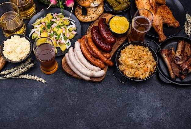 Pratos da oktoberfest com pretzel de cerveja e linguiça Foto Premium