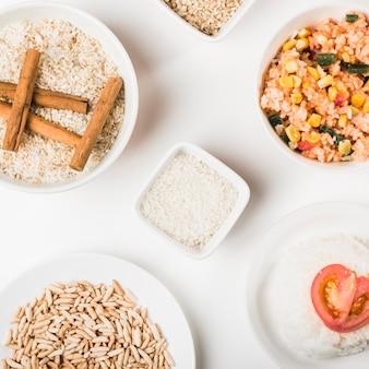 Pratos de arroz com tigelas de arroz crus no fundo branco