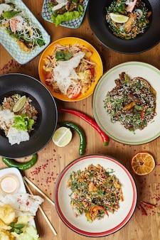 Pratos de comida asiática na mesa de madeira