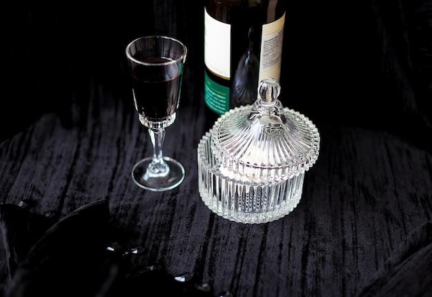 Pratos de doces, garrafa e um copo de vinho tinto em um fundo preto
