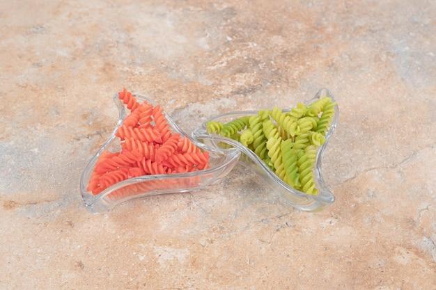 Pratos de dois copos cheios de macarrão espiral colorido no espaço de mármore.