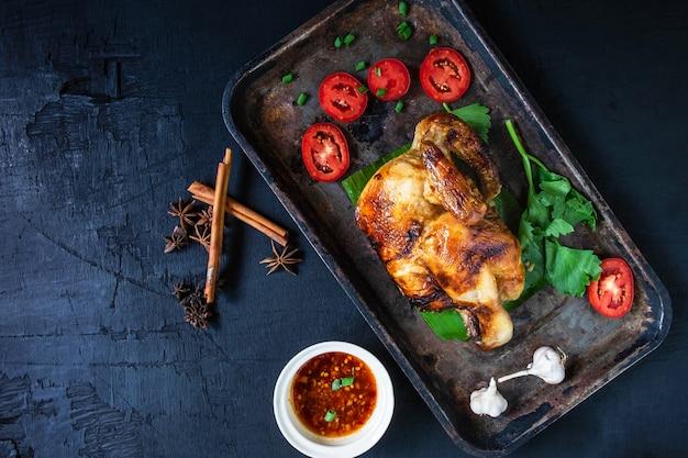 Pratos de frango grelhado e molho de mergulho do forno em preto