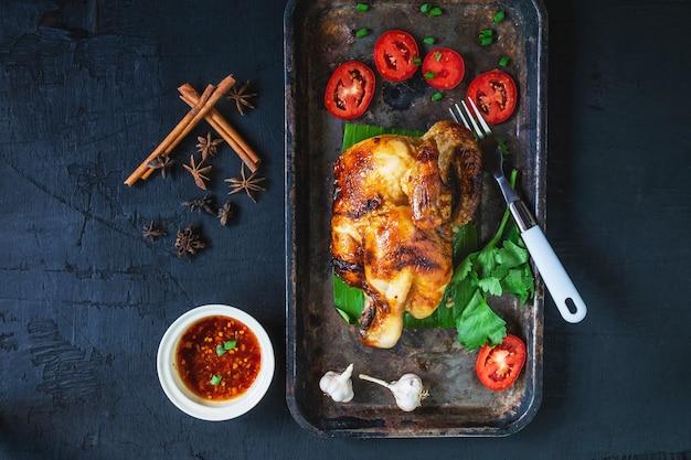 Pratos de frango grelhado e molho de mergulho do forno em um fundo preto