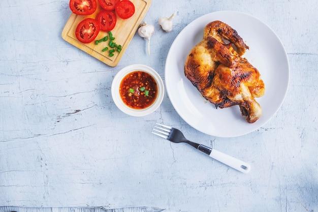 Pratos de frango grelhado e molho sobre um piso de madeira branca