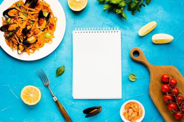 Pratos de frutos do mar planos com notebook