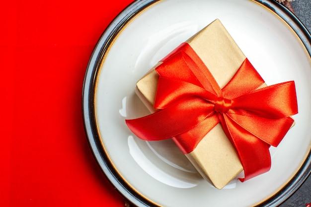 Pratos de jantar com presente em forma de arco com fita em um guardanapo vermelho sobre fundo escuro