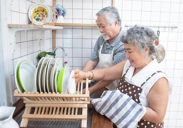 Pratos de lavagem dos pares superiores felizes asiáticos mais velhos no dissipador em casa na cozinha em casa.