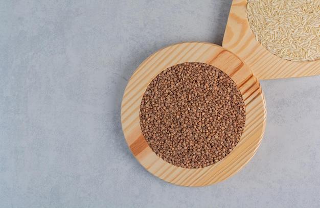 Pratos de madeira cheios de arroz e trigo sarraceno na superfície de mármore