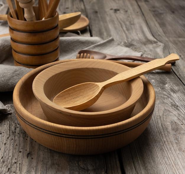 Pratos de madeira redondos vazios e colheres em uma mesa cinza, vista superior