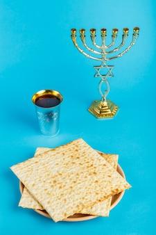Pratos de matzo colocados por magen dovid em uma superfície azul e uma taça de vinho para kidush e menorá