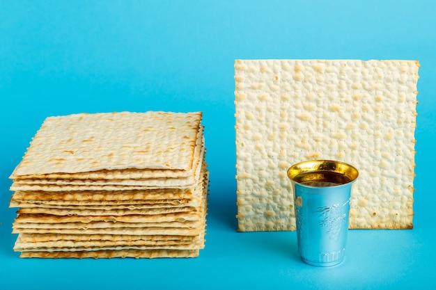 Pratos de pão ázimo colocados uns sobre os outros em uma superfície azul e uma taça de vinho para kidush