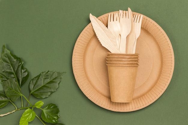 Pratos de papelão descartáveis. garfos e colheres de madeira. prato ecológico