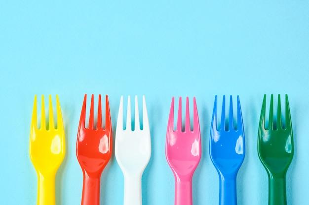 Pratos de plástico coloridos em um espaço azul. o conceito de poluição ambiental por plástico, lugar de ecolog para texto, plano leigos